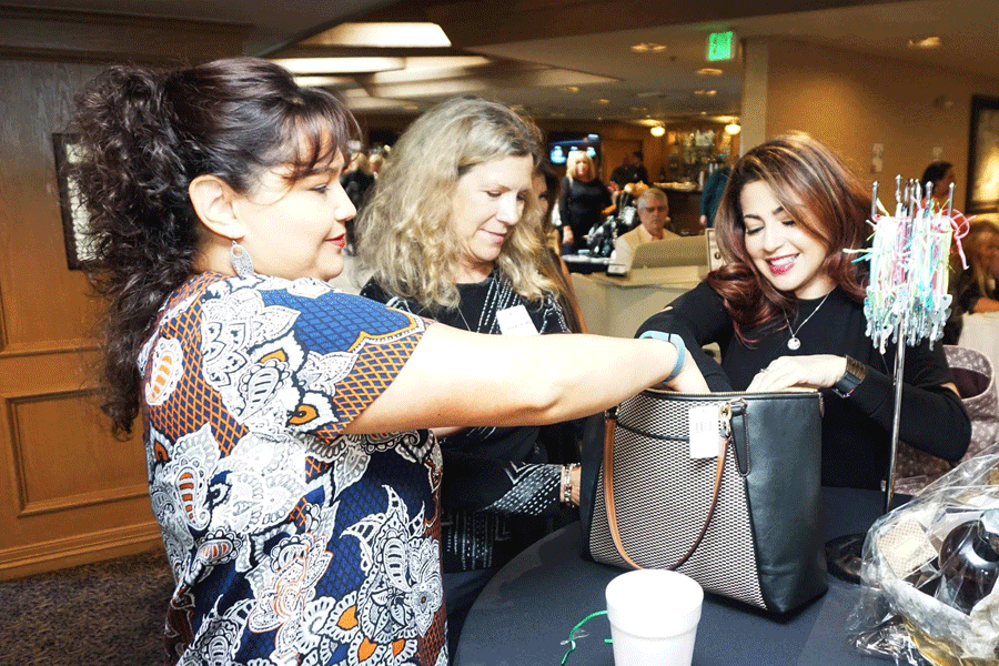006 Noemi Gonzalez l and Valerie Willett mid helping a guest try to unlock the Treasure Purse